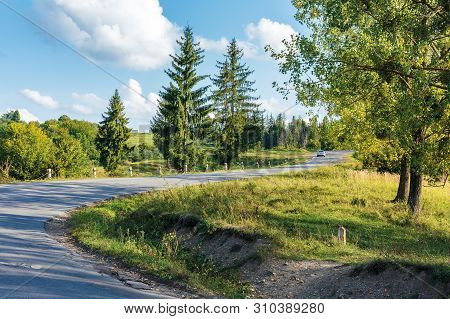 Old Serpentine Road Uphill Through Forest. Beautiful Transportation Evening Scenery. Fluffy Clouds O