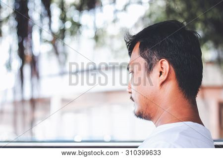 A Lonely Man Sitting Back And Being Absent-minded Against Blurred Outdoor Background