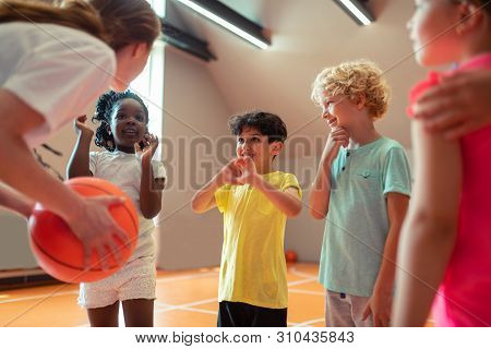 Children Smiling To Their Sports Teacher In The Gym.