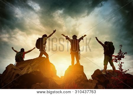 Celebrating Life Of Hikers Climbing Up Mountain Cliff. Climbing Group Helping Each Other While Climb