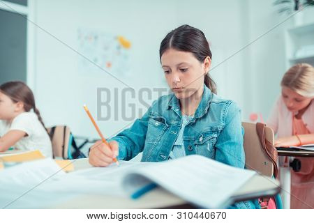 School Girl Looking Anxiously At Her Maths Test.