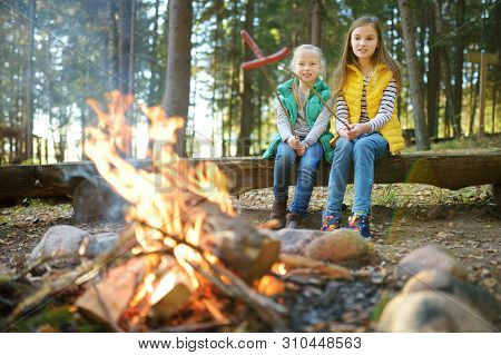 Cute Young Sisters Roasting Hotdogs On Sticks At Bonfire. Children Having Fun At Camp Fire. Camping