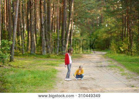 Two Cute Young Sisters Having Fun During Forest Hike On Beautiful Summer Day. Children Exploring Nat