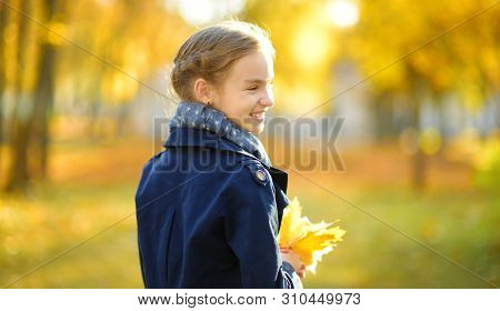 Adorable Young Girl Having Fun On Beautiful Autumn Day. Happy Child Playing In Autumn Park. Kid Gath