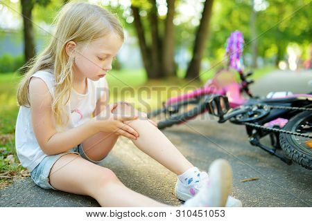 Cute Little Girl Sitting On The Ground After Falling Off Her Bike At Summer Park. Child Getting Hurt