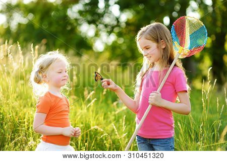 Two Little Sisters Catching Butterflies And Bugs With Their Scoop-nets. Kids Exploring Nature On Sun