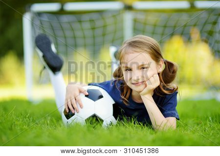 Cute Little Soccer Player Having Fun Playing A Soccer Game On Sunny Summer Day. Sport Activities For