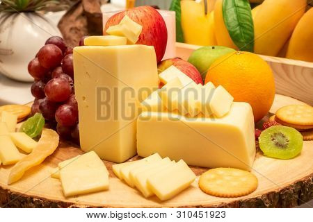 edam cheese with variety of fruit and cracker on wooden plate in buffet line