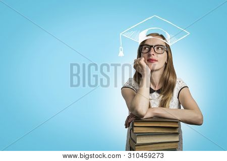 Young Girl Student Leaning On A Pile Of Books And Looking Up On A Blue Background. A Painted Student