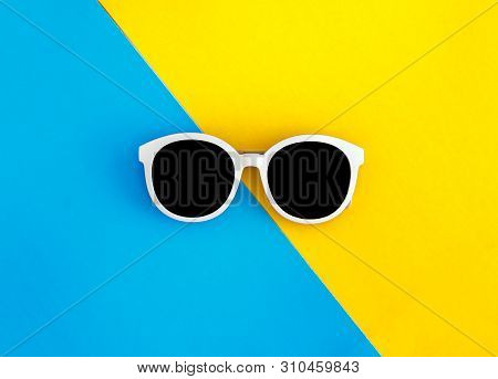 Sunny Stylish White Sunglasses On A Bright Blue-cyan And Yellow-orange Background, Top View, Isolate