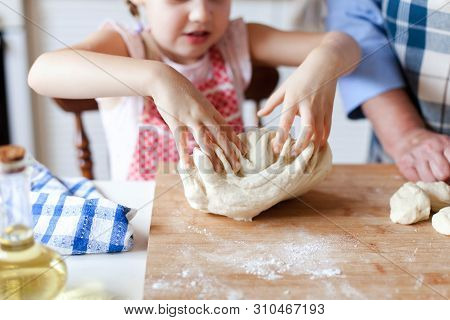 Kid Is Playing With Dough. Family Is Cooking In Kitchen. Child Is Baking Homemade Pastries Or Pizza.