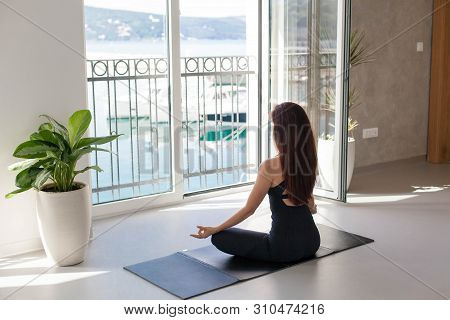 Young Woman Is Practicing Yoga In Front Of Big Opened Window With View Of Sea Beach, Mountains. Girl