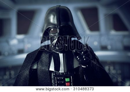 JULY 7 2019: Star Wars Sith Lord Darth Vader in the Death Star looks to camera, force choke hold - Hasbro action figure