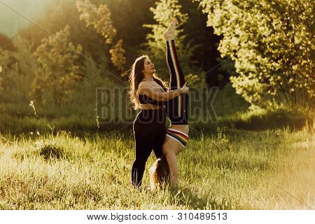 Two Beautiful Women With Long Hair Doing Yoga In Nature On A Sunny Summer Day. Body Positive, Sports