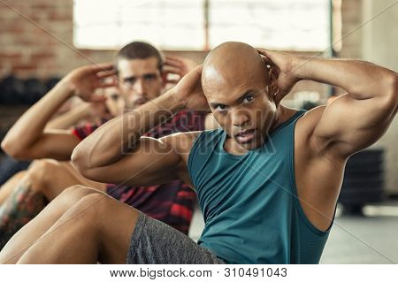 Muscular african american man doing sit ups at gym with other people in background. Mature black man doing abs workout with class at gym. Muscular guy doing crunches.