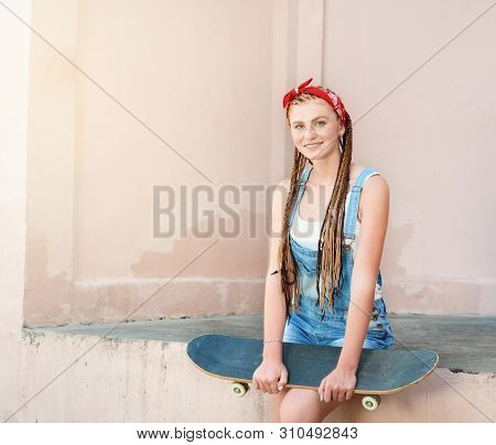 Red Hair Teenage Girl With Freckles In Casual Style With Skateboard In Summer Day On The Street