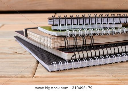 Stack Of Spiral Notebooks On Wooden Background. Pile Of Paper Notepads With Ring Binding On Wood Tab