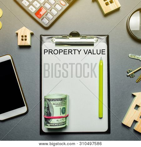 Table with wooden houses, calculator, coins, magnifying glass with the word Property value. The contract for real estate appraisal. Rate the property. Valuation house. Appraisal Services. Flat lay poster