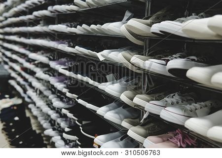 Side View Of Shoe Store Shelves With Of Lots Of Sneakers On Sale. Low-budget Comfortable Footwear Sh