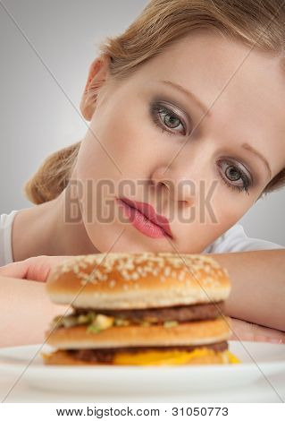 Beautiful Girl Sits On A Diet,  Sad To Looking At A Hamburger