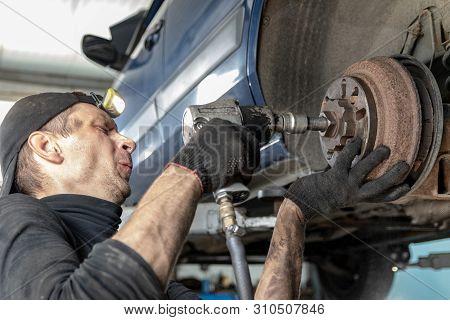 Car Mechanic Repairs The Rear Brake Drum, Unscrews With A Pneumatic Gun.