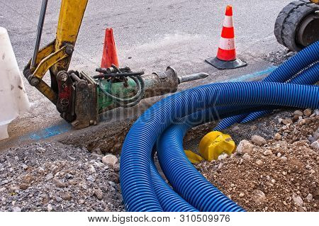 Construction Site, Road Work. Hydraulic Crushing Hammer. Plastic Pipes For Electric Cables.