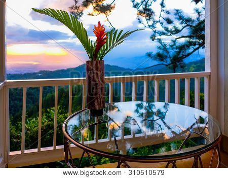 Single Red Ginger In A Vase On A Glass Table Facing The Sunset Over The Blue Mountains, Jamaica