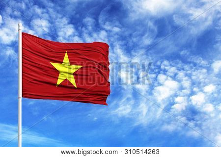 National Flag Of Vietnam On A Flagpole In Front Of Blue Sky