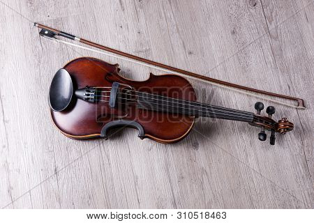 Classical Violin Isolated On Wooden Background. Studio Shot Of Old Violin. Classical Musical Instrum