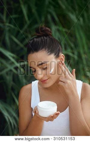 Beauty Concept. Woman Holds A Moisturizer In Her Hand And Spreads It On Her Face To Moisturize Her S