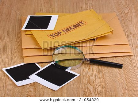 Envelopes with top secret stamp with photo papers and magnifying glass on wooden background