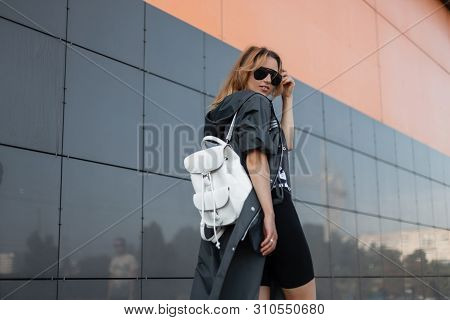 Beautiful Young Hipster Woman In Fashionable Clothes In Sunglasses With Stylish Backpack Walks Along