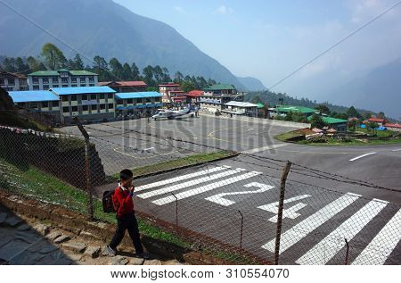 Lukla, Nepal - May 8, 2019: Boy walking to school next to fence of Tenzing–Hillary airport in Himalayas mountains