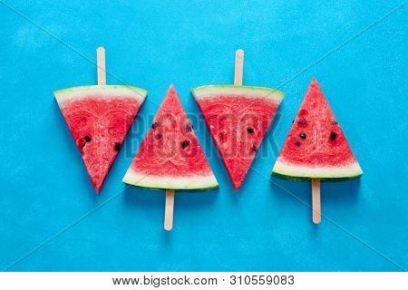 Fresh watermelon slices on sticks (seen from above).