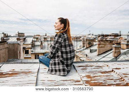 A Girl On The Roof Of A House In Solitude Meditates Or Enjoys Life Or A Digital Detox. The Search Fo