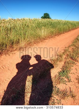 People Shadows On Old Dusty Road With Ferric Red Soil.  Shadows Of Walking Pedestrians Projected On