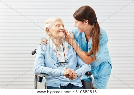 Caring care woman in the elderly care for a senior citizen in a wheelchair