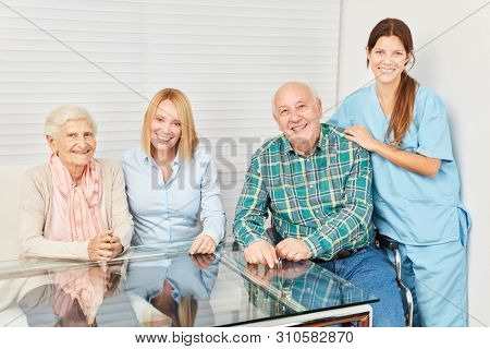 Happy family with senior couple and nurse in a retirement home