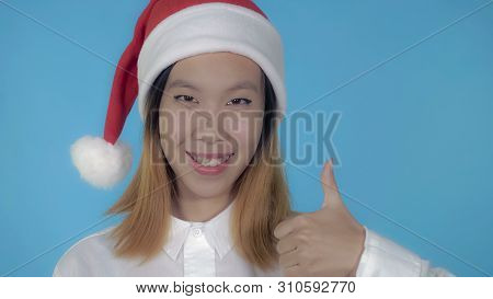 Close Up Portrait Young Asian Woman Shows Symbol Like Wearing Santa Claus Hat On Blue Background In