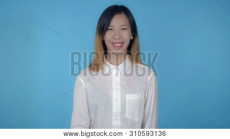 Young Asian Happy Woman Posing Showing Positive Emotions On Blue Background In Studio. Attractive Mi