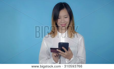 Young Asian Woman Using Smartphone For Buying Online Or Pay Order Or Bills On Blue Background In Stu