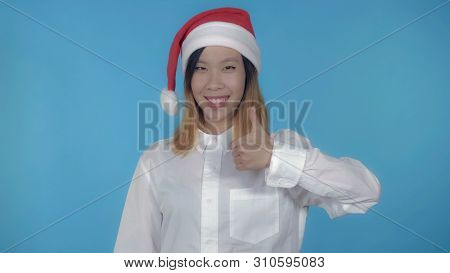 Young Asian Woman Posing Wearing Santa Claus Hat Showing Symbol Hand Gesture Like On Blue Background