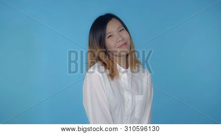 Young Asian Woman Posing Flirting On Blue Background In Studio. Attractive Millennial Girl Wearing W