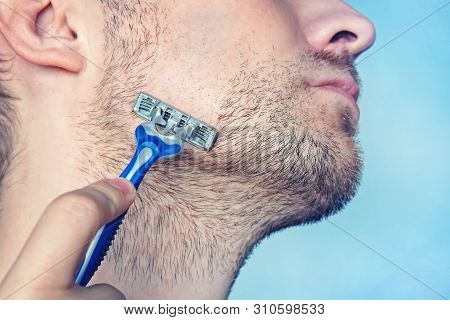 Handsome Young Man With Foam On His Face Is Shaving Using A Razor, On Blue Background. A Man Shaves