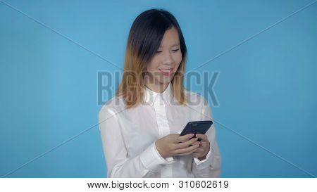 Young Asian Woman Messaging On Mobile With Touch Screen On Blue Background In Studio. Attractive Mil