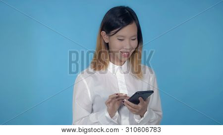 Young Asian Woman Using Smartphone For App Or Social Media On Blue Background In Studio. Attractive