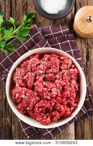 Fresh Raw Ground Or Minced Beef Meat In Bowl, Seasonings (salt And Pepper) And Fresh Parsley On The
