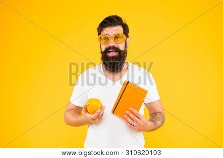 Being Proud Of Geek In You. Geek Man. Bearded Man In Geek Glasses Holding Orange And Book On Yellow