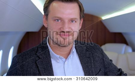 Businessman portrait in private jet. Well dressed, confident male caucasian entrepreneur smiling inside of business airplane cabin.