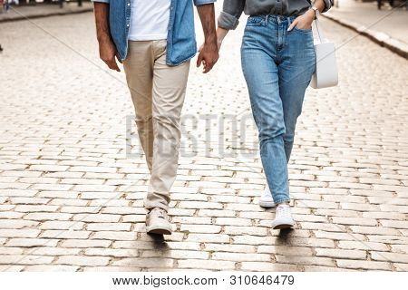 Cropped image of a young couple in love walking outdoors at the city street